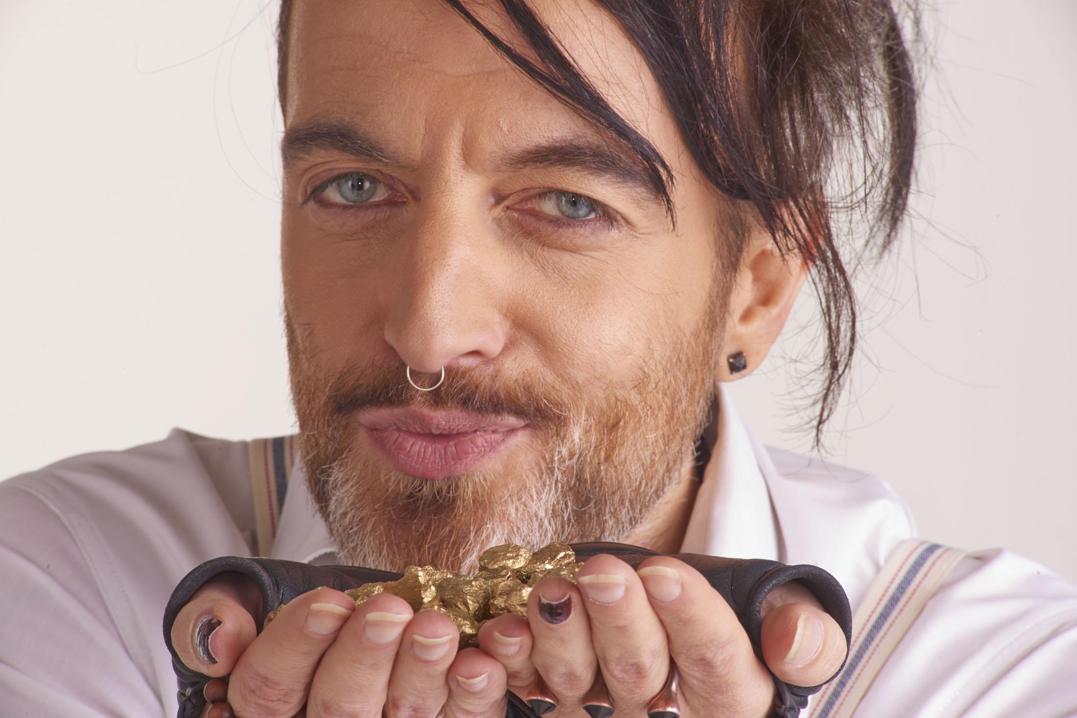 Gros plan d'un visage d' homme soufflant sur de pépites d'or