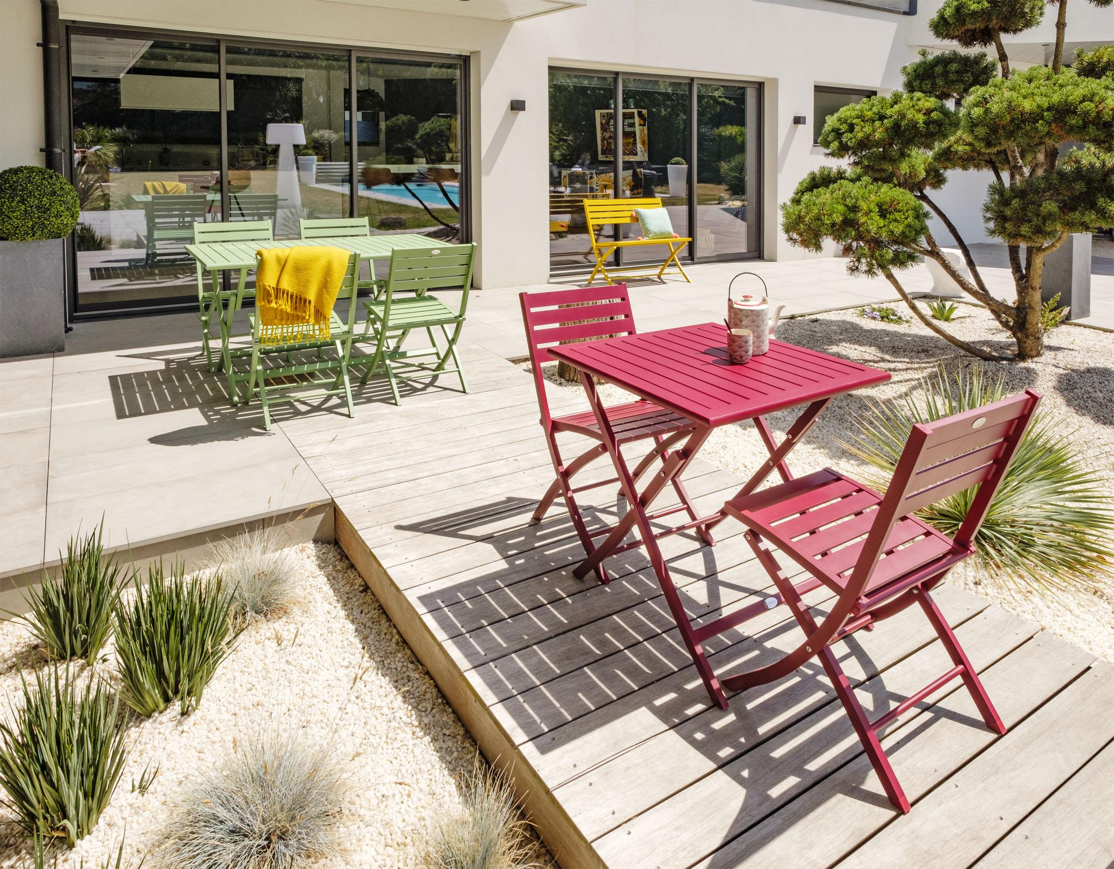 ambiance extérieur de tables de jardins de plusieurs couleurs avec leurs chaises sur une grande terrasse