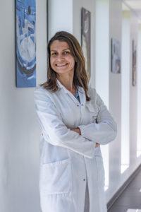 Portrait couleur d'une femme de laboratoire en blouse blanche dans un couloir, Société VMI