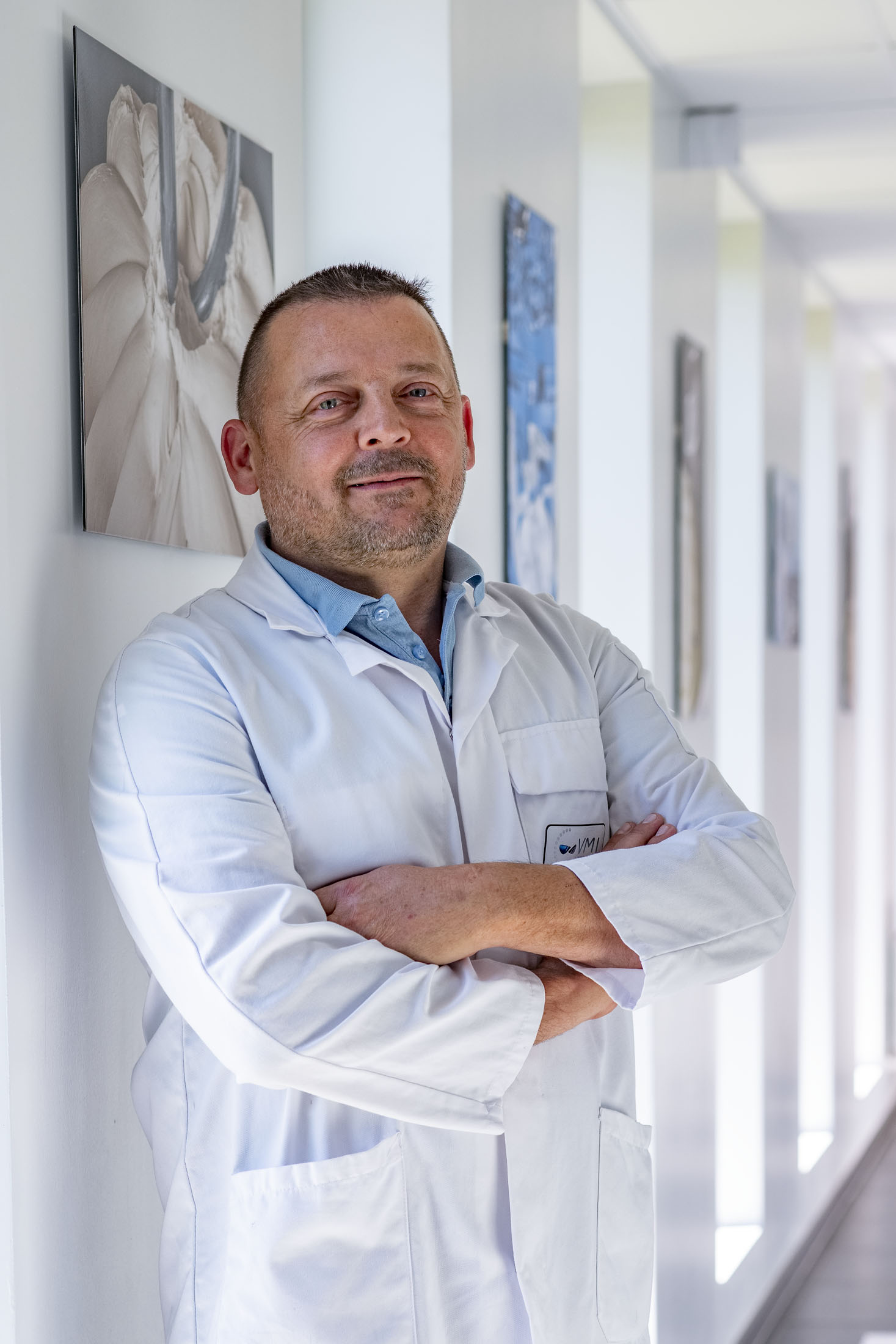Portrait couleur d'un homme de laboratoire en blouse blanche dans un couloir, Société VMI