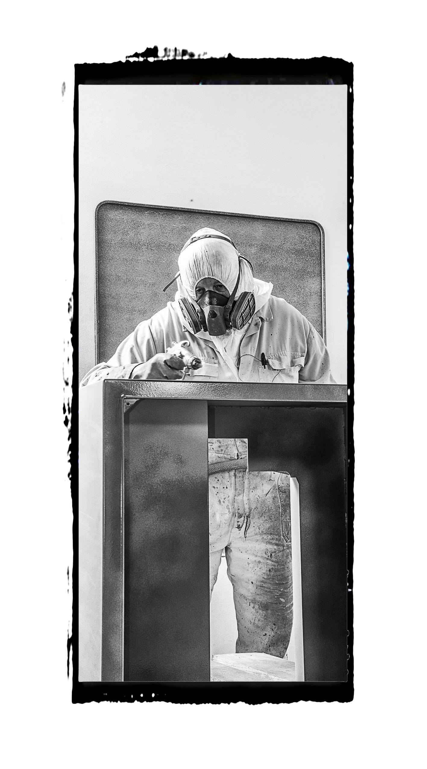 Portrait Noir et blanc d'un peintre dans une cabine de peinture industriel avec son équipement de protection