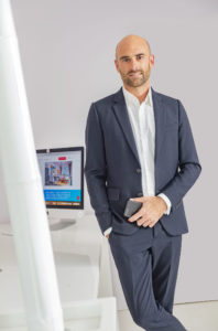 Portrait couleur d'un dirigeant en costume debout devant son bureau