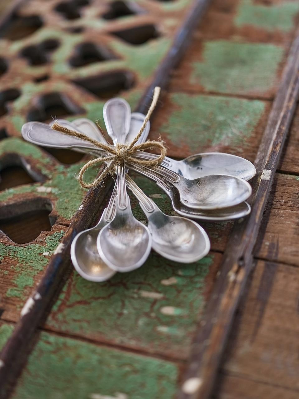cuillière attachées avec ficelle sur pièce de bois